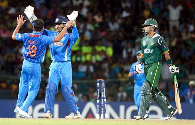 Virat Kohli, left, and MS Dhoni celebrate the dismissal of Pakistan's batsman Mohammad Hafeez