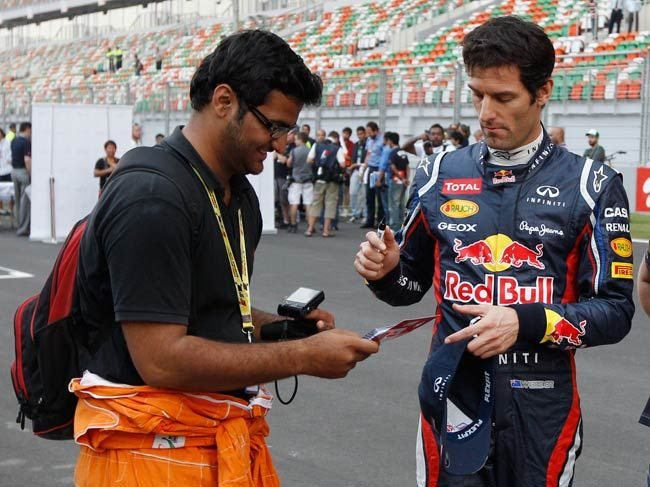 Mark Webber of Red Bull signs an autograph for a fan