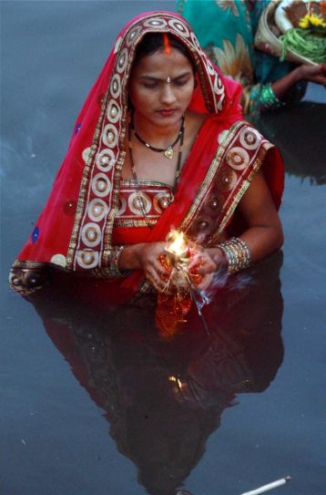 Woman prays during Chhath Puja