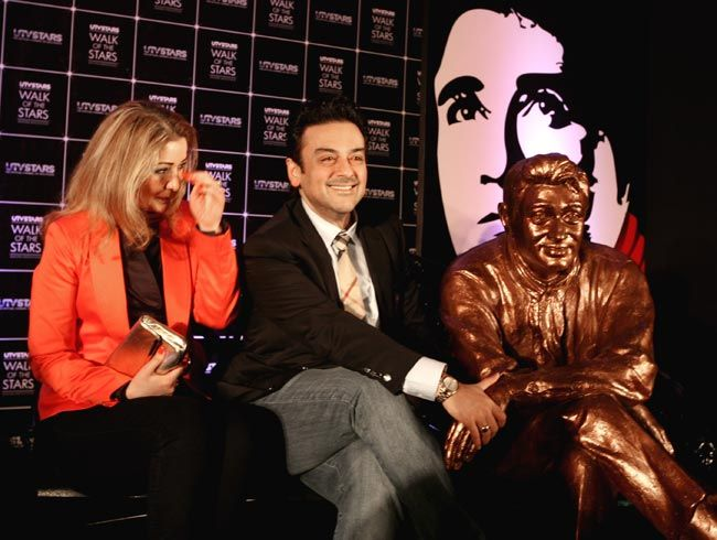 Adnan Sami and his wife Roya Faryabi with Dev Aanand's statue.