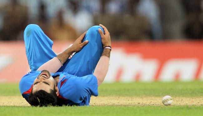 Virat Kohli lies on the ground in pain.