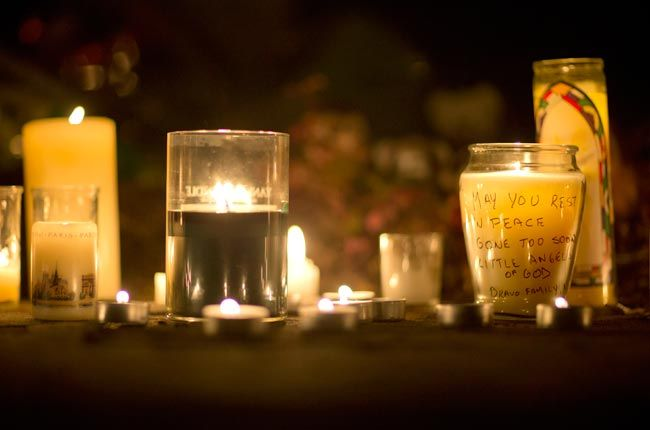 A message is seen on a candle outside the St. Rose of Lima Roman Catholic Church in Newtown, Connecticut.