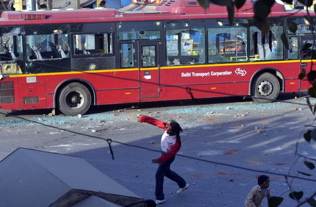 A youth pelts stone at a stranded DTC bus in Mangolpuri