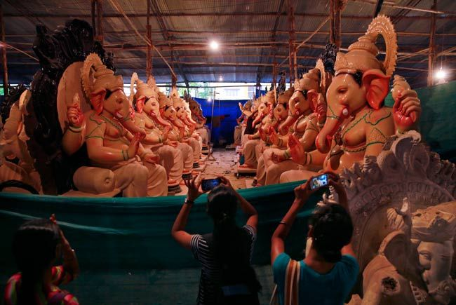 People take the picture of idols of Hindu god Ganesha being prepared at a studio in Mumbai, India, Tuesday, Aug.5, 2014.