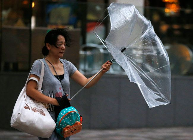 Woman struggling with an umbrella.