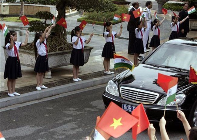 Vietnamese schoolgirls wave Vietnamese and Indian flags