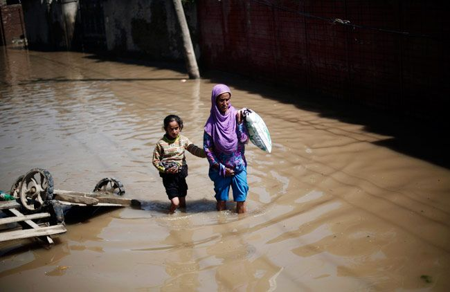 A woman and her daughter wade through a flooded street