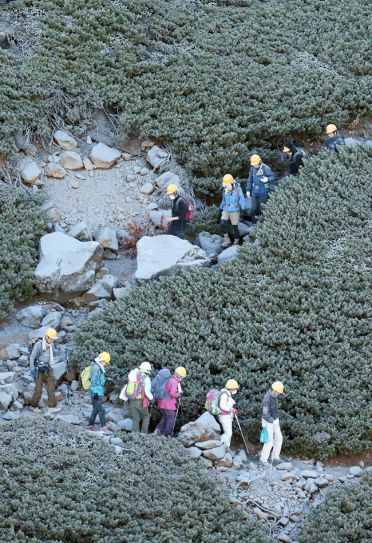 Climbers descend down ash-covered Mount Ontake.