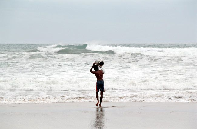 A man pours sea water on himself as he performs a ritual for safety ahead of cyclone Hudhud