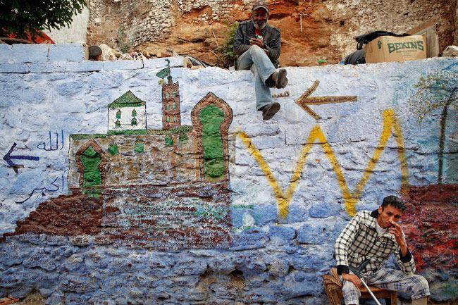 Men sit on a painted wall behind Bab el Bahr gates of Rabat's Medina