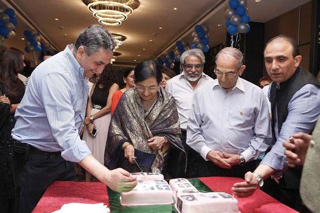 Bikramjeet's mother cuts the cake.