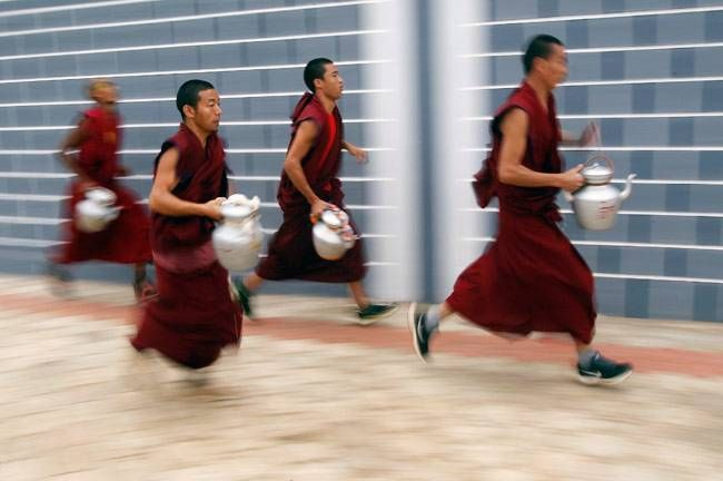 Buddhist monks carrying kettles run towards the monastery to serve tea to attendees of the Jangchup Lamrim teachings conducted by the Tibetan spiritual leader the Dalai Lama (unseen) at the Tashi Lhunpo Monastery in Bylakuppe in the southern state of Karn