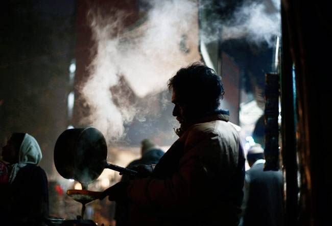 A vendor prepares tea at his roadside stall on a cold winter evening in New Delhi January 29, 2014.