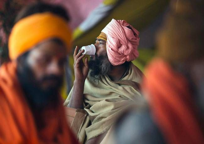 "A sadhu, or Hindu holy man, drinks tea along the banks of the Ganges river ahead of the ""Kumbh Mela"" (Pitcher Festival), in the northern Indian city of Allahabad January 11, 2013."