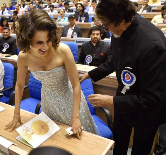 Amitabh making way for Kangana Ranaut as her name is announced at the event.