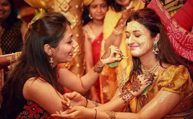 Divyanka is all smiles with her eyes close as a friend applies haldi to her.