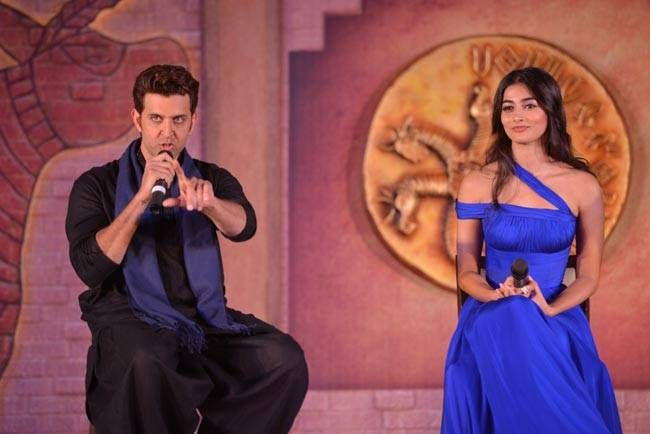 Hrithik Roshan speaking to the press with Pooja Hegde alongside her.