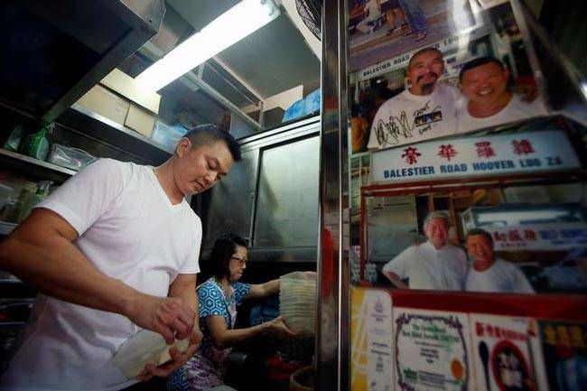 Hawker Stan Lim, 43, prepares his ingredients at Michelin Bib-Gourmand-awarded Balestier Road Hoover Rojak, at Whampoa Food Centre. The photograph (R) shows Hong Kong celebrity Chow Yun-Fat (top left) posing with Stan's father, Lim Ngah Chew, as Stan open