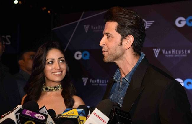 Yami Gautam looks at Hrithik Roshan while he is talking to the media.