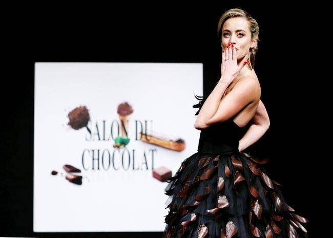 A model blows a kiss towards the crowds as she walks the ramp in a chocolate outfit. The simple black gown turned gorgeous with the delicate chocolate leaves.