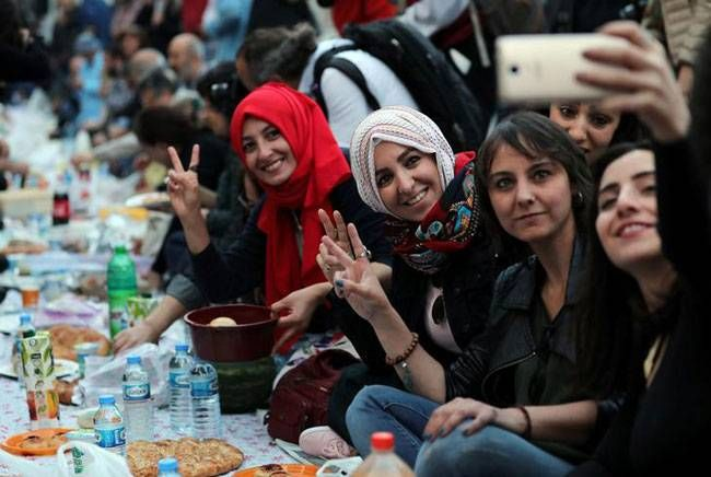 People pose for selfie as they break their fast at the main shopping and pedestrian street of Istiklal in central Istanbul, Turkey.