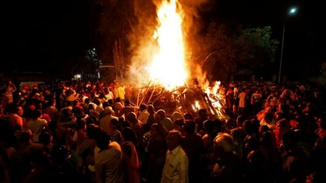 "Hindu devotees walk around a bonfire during a ritual known as ""Holika Dahan"" which is part of Holi festival celebrations, in Ahmedabad"