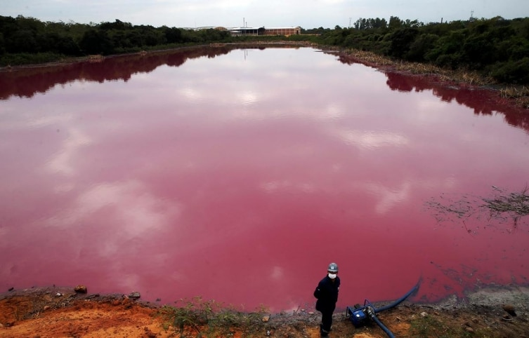 A worker stands by a pump as he extracts water for testing from Cerro Lagoon, which is pink and smells foul due to untreated waste allegedly dumped by the Waltrading SA tannery company, in Limpio, Paraguay, Wednesday, September 2, 2020
