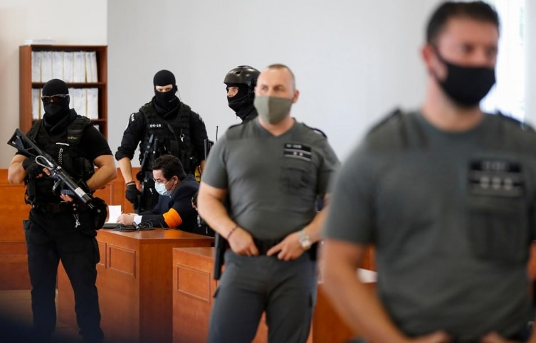 Marian Kocner is surrounded by armed police officers in the courtroom after a trial against him in Pezinok, Slovakia, Thursday, September 3, 2020