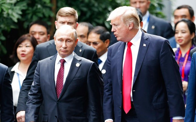 US President Donald Trump, right, and Russia's President Vladimir Putin talk during the family photo session at the APEC Summit in Danang, Vietnam. (Photo: AP)