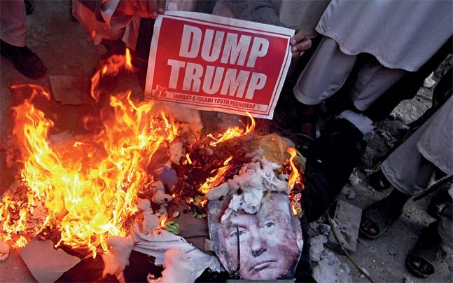 Jamaat-e-Islami supporters burn a poster of Trump in Peshawar
