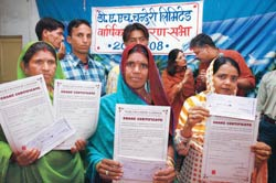 Community ownership: Weaver-women holding share certificates in their hands