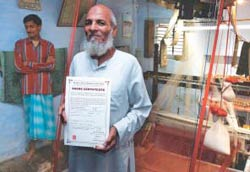 Stronger supply-base: A weaver in front of his loom, holding a share certificate
