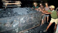 Mine workers push a coal cart inside a mine in Dhanbad, Jharkhand