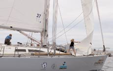 The crew attempts to roll and change the sails on a particularly windy day.