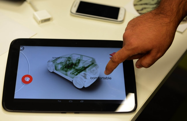 Harsha Padmanabha from Visarity demonstrates a 3D car advertisement on a tablet