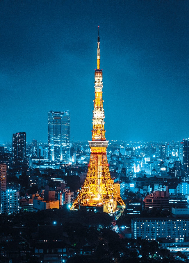 The old Tokyo tower, like a lighthouse, beams over the city's skyline