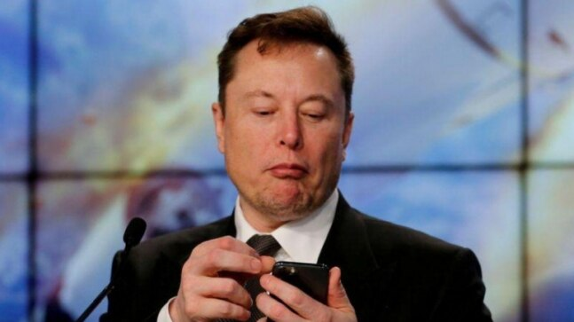 SpaceX founder and chief engineer Elon Musk looks at his mobile phone during a post-launch news conference (Image: Reuters)
