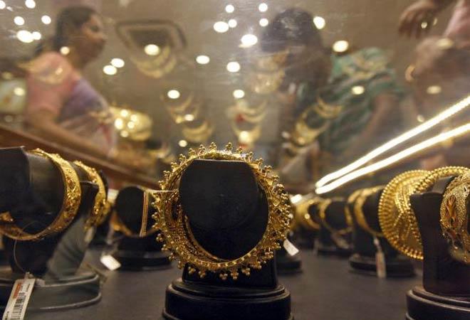Gold prices edge down on global cues, sluggish demand