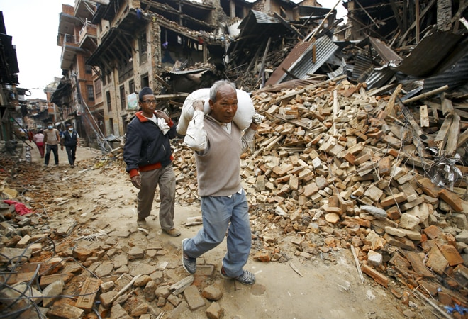 A man carrying goods walks along a street with houses that were collapsed by an earthquake at Bhaktapur, Nepal, on April 30, 2015.