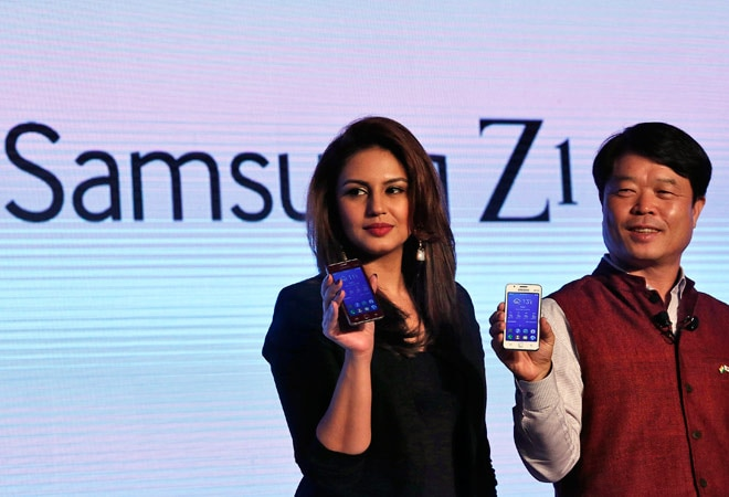 Samsung's Hyun Chil Hong (R) and actress Huma Qureshi hold Samsung's new Z1 smartphones at its launch