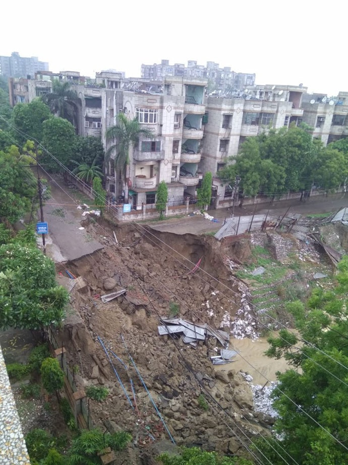 In Ghaziabad, a big portion of a road caved in, putting apartment blocks nearby in danger of collapse.