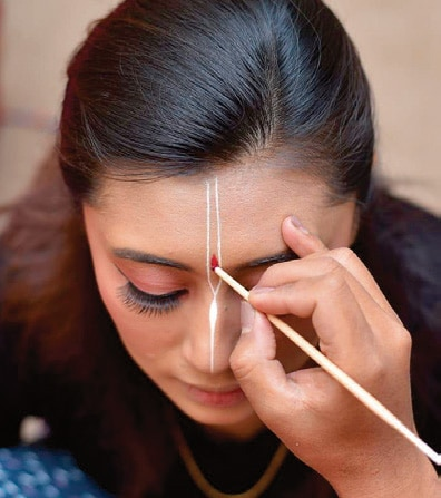 Sandalwood being painted on Reena's forehead.