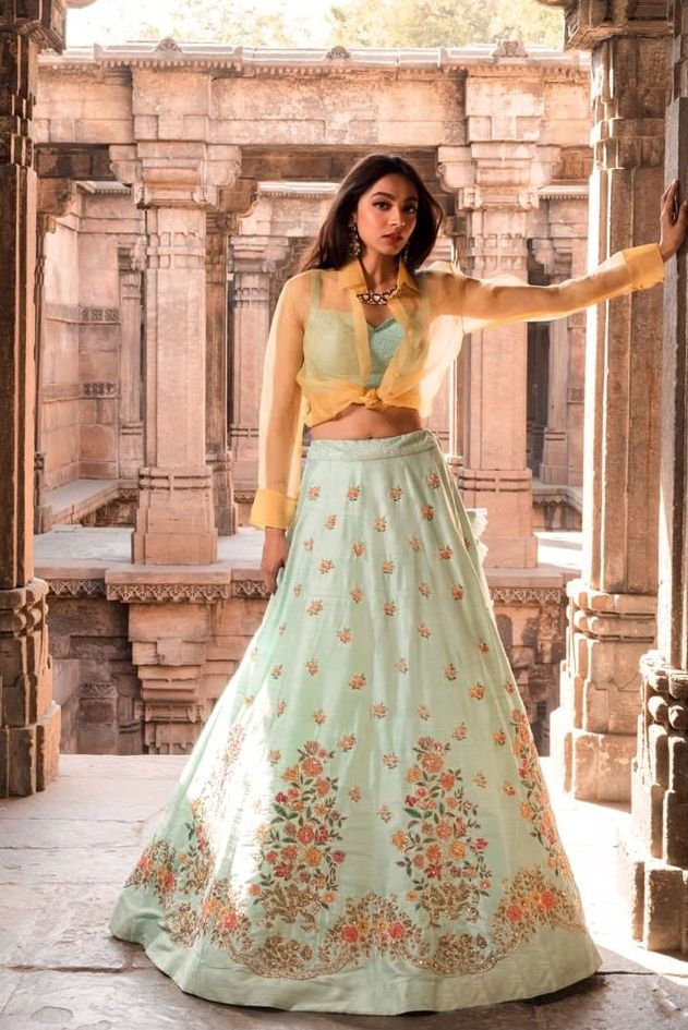 The alluring dazzle of the mint raw-silk lehenga with multicolour resham embroidery, is teamed with a bustier layered with a soft tulle collar shirt