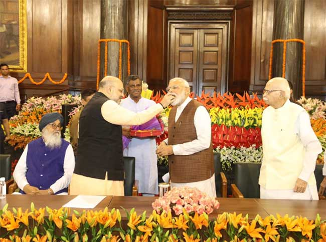 amit shah offers victory sweet to narendra modi
