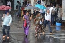 Mumbai  People shield themselves with umbrellas as rain lashes Mumbai on June 7  2018  Photo  IANS
