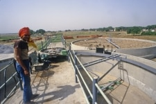 WORKER STANDING OVER EFFLUENT TREATMENT PLANT