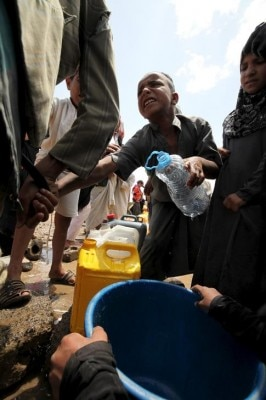 A boy fights for his turn to fill a jerrycan with water from a public tap, amidst water shortages in Sanaa May 13, 2015. A five-day humanitarian truce in Yemen appeared to be broadly holding on Wednesday, despite reports of some air strikes overnight by Saudi-led forces and continued actions by the country's dominant Houthi group in the east. REUTERS/Mohamed al-Sayaghi