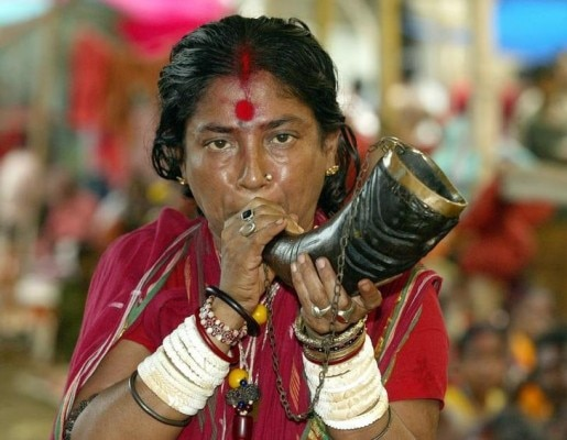 An Indian Hindu woman priest plays an instrument made from buffalo horn at the Kamakhya Temple in the northeastern Indian city of Guwahati June 22, 2003. Seers and pilgrims are arriving at the temple, which is famous for the teaching of black magic known traditionally as 'Tantra', for the annual four day 'Ambubachi Mela', which starts on June 22 when pilgrims and Seers believe their prayers will be answered during the festival.