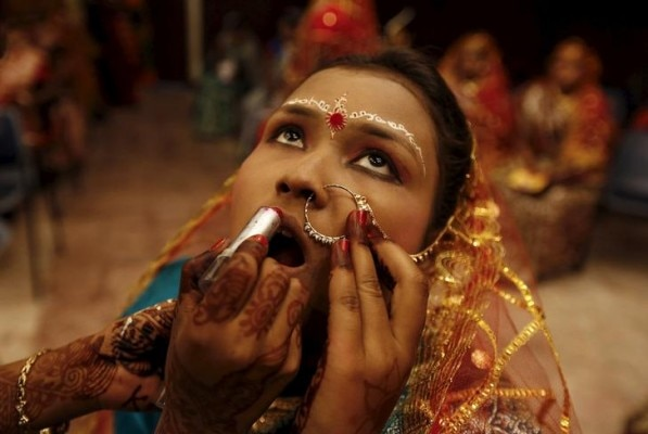 A bride gets her make-up done before the start of a mass marriage ceremony in Kolkata, India, February 14, 2016. A total of 150 tribal Hindu, Muslim and Christian couples from various villages across the state took their wedding vows on Sunday during the day-long mass marriage ceremony organised by a social organisation, the organisers said. REUTERS/Rupak De Chowdhuri TPX IMAGES OF THE DAY