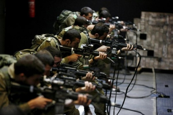 Israeli soldiers respond with laser-firing rifles to a simulated Palestinian attack playing out on an interactive screen, during an open-fire scenario training in Camp Tsur infantry training base in southern Israel, near Yeruham March 24, 2016. REUTERS/Amir Cohen